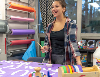 Student crafting in colorful DIY Craft Room